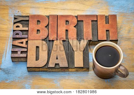 Happy Birthday greeting card - word abstract in vintage letterpress wood type blocks against grunge wooden background with a cup of coffee