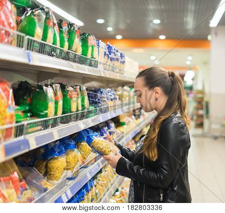 woman housewife chooses pasta or macaroni in the supermarket