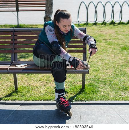 Pretty Roller girl unscrewing wheels on freeskate roller Skates with Allen key or Hex key tool. Maintenance of professional skates