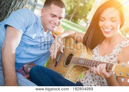 Happy Mixed Race Couple at the Park Playing Guitar and Singing Songs.