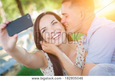 Happy Mixed Race Couple Taking Self Portrait with A Smart Phone in the Park.