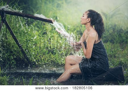 Beautiful young woman takes bath naturally flows from the bamboo chute