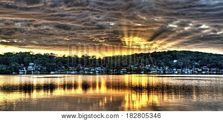 Golden Crepuscular sunrise water reflections. An inspirational colourful panoramic orange and gold sunrise photo with vivid sun rays and bold cloudscape water reflections in the tranquil waters of Kilabin Bay. Lake Macquarie Photo NSW Australia.