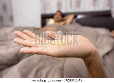 Woman showing a condom on bed Focus on the condom in the foreground
