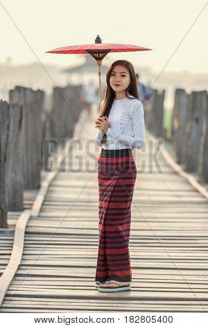 Burmese woman holding traditional red umbrella and walking on U Bein Bridge Myanmar