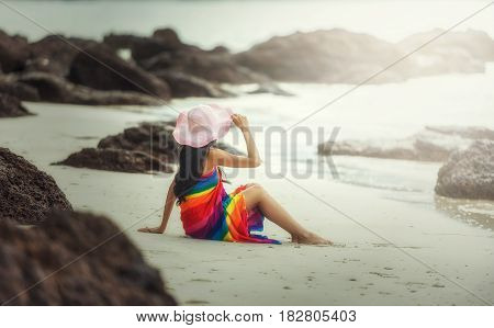 Happy woman enjoying beach relaxing joyful in summer by tropical sea. Beautiful model happy on travel wearing beach sun hat on beach