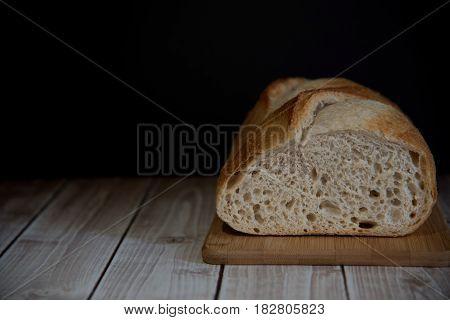 Sourdough homemade bread on the wooden board dark photo copy space.