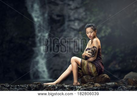 Beautiful young woman takes bath at the nature