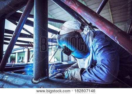 Industrial Worker at the factory welding welding steel pipe structure