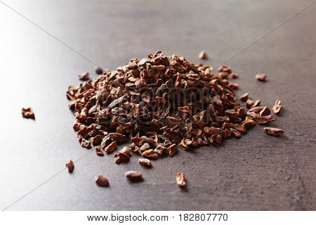 Heap of aromatic cocoa nibs on gray background