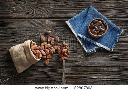 Bowl and spoon with aromatic cocoa beans on wooden background