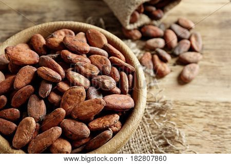 Bowl with aromatic cocoa beans on wooden table