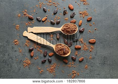Spoons with aromatic cocoa powder and beans on gray background
