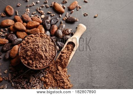 Bowl and wooden scoop with aromatic cocoa powder on gray background