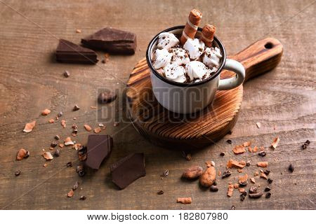 Cup of hot cocoa with marshmallows on wooden table