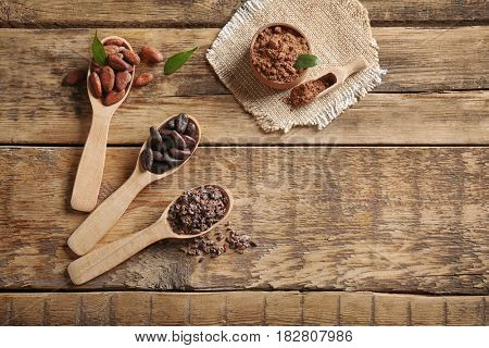 Spoons with aromatic cocoa beans and nibs on wooden table