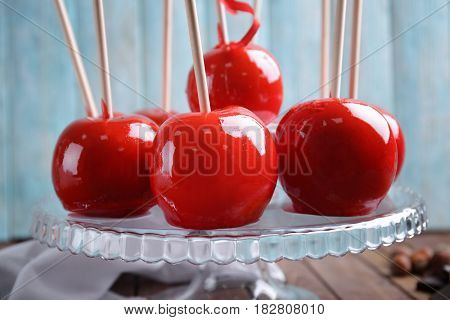 Delicious toffee apples on glass stand, closeup