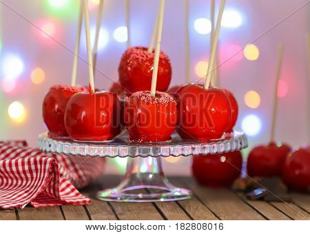 Delicious toffee apples on glass stand against fuzzy background