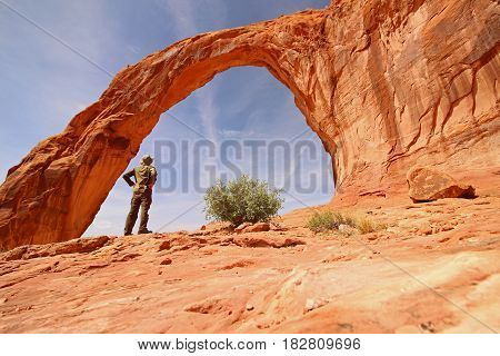 A hiker marvels at the Corona Arch in Utah.