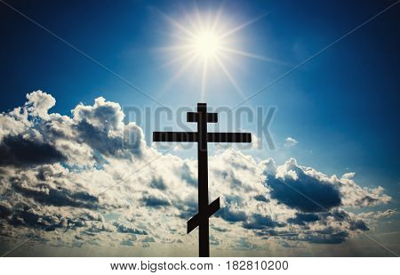 Orthodox christian cross silhouette with blue sky and bright sun
