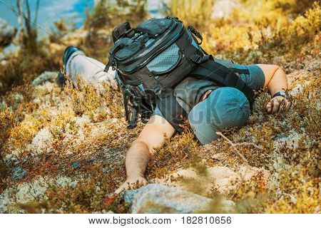 Young man tourist lying exhausted on ground and feeling bad. Danger accident concept.