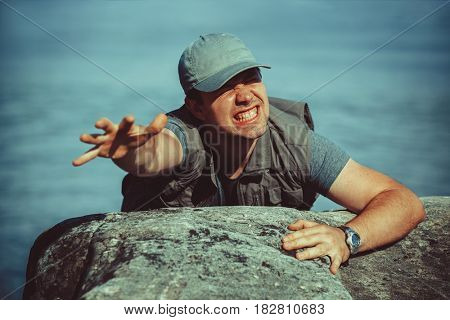Young man tourist surviving falling from stone to water and trying to climb up