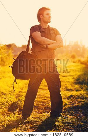 Young man tourist with big shoulder bag standing at sunset light