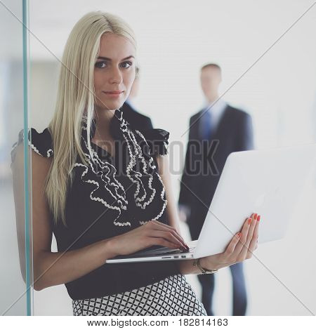 Young businesswoman holding a laptop, standing on office .