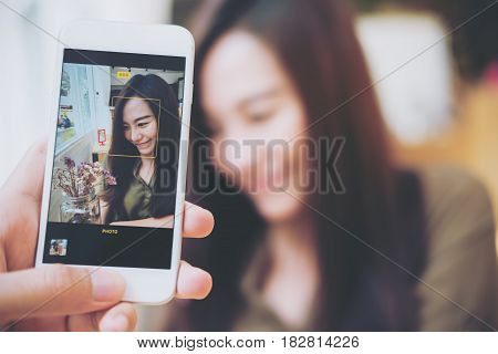 A man using white smart phone taking a picture of a beautiful woman in wooden vintage cafe