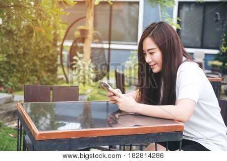 A beautiful asian woman enjoy using on smart phone with feeling relax and smiley face in outdoor and green nature background