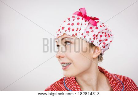 Funny happy woman after shower wearing pink pajamas and dotted bathing cap