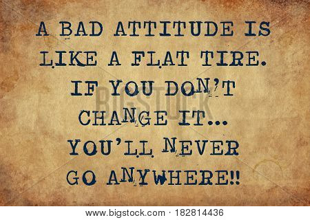 Inspiring motivation quote with typewriter text a bad attitude is like a flat tire. if you don't change it...you'll never get anywhere. Distressed Old Paper with Typing image.