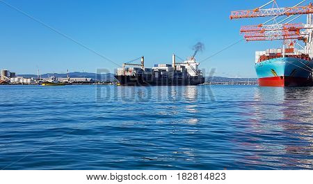 Tauranga New Zealand - April 19, 2017;  Port of Tauranga container terminal with tall white and orange cranes stretching up and out over moored ship as freighter leaves port lead by yellow pilot boat.