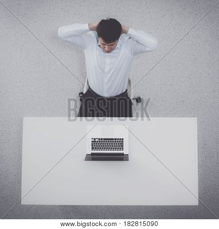 Young man working on laptop, sitting the desk in office.
