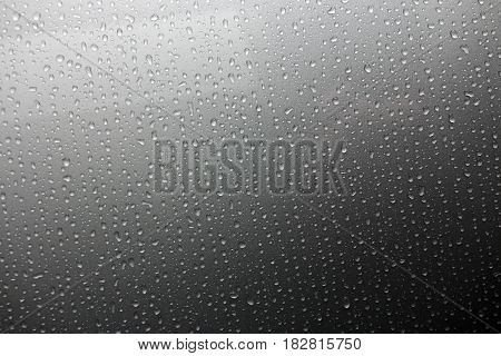The background of a drop of rain drips down the glass