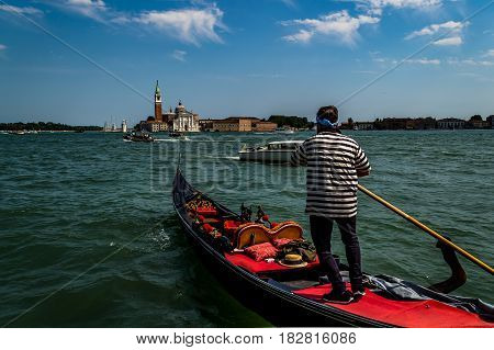 Venetian Gondolier and the panorama of San Giorgio Maggiore viewed from the main island