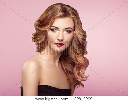 Blonde woman with long and volume shiny wavy hair . Beautiful model with curly hairstyle. Perfect make-up. Beauty style model