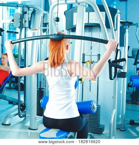 Young woman doing fitness exercises with expander.