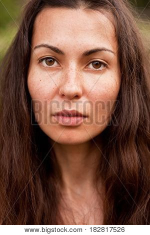Portrait of a young beautiful brunette with Freckles