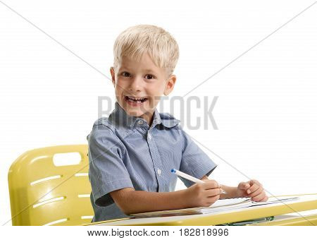 Portrait of cheerful laughing young schoolboy sitting at the desk