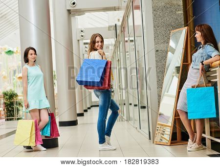 Happy woman with shopping bags posing in front of miror