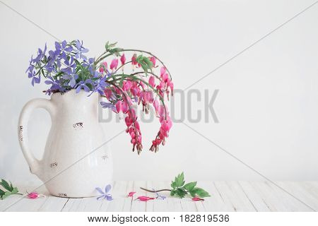 the flowers in jug on white background