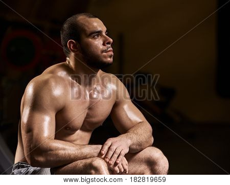Young muscular tired sportsman relaxing after training in gym
