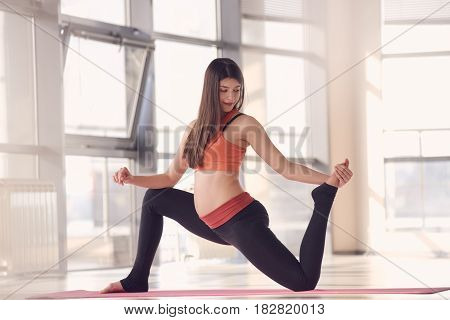 Beautiful young pregnant woman doing complex of physical exercises
