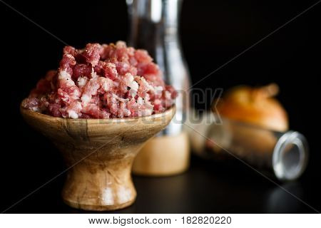 Chopped meat in a wooden bowl with spices on a black background