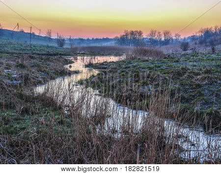 The stream in the hollow in March in the Krasnodar region. Orange sunrise in the sky, and the grass is covered with white bloom from the morning frost.