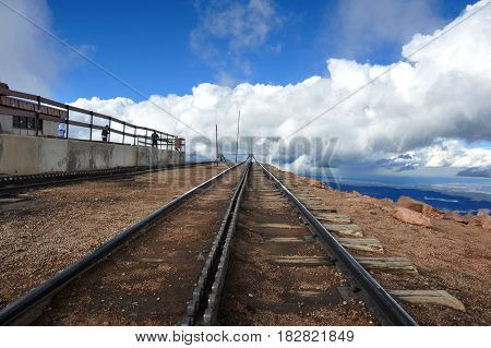 Train tracks atop Pikes Peak end abruptly at the edge of a cliff high above the valley below