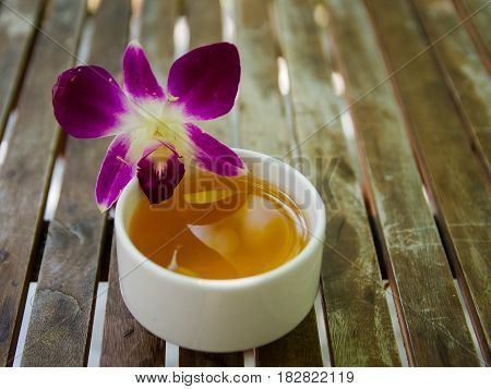 Violet dendrobium orchid flower on a jasmine ceramic tea cup on wooden table