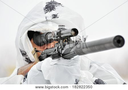 A soldier in a white camouflage cape looks into the rifle sight