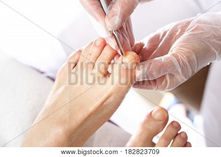Nail cleaning in the beauty salon Pedicure. Nail clipping at the feet. Pedicure, cutting skins. Beautician performs pedicure, cleans and cuts fingernails at the feet